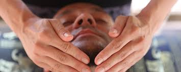Reiki practitioner with hands under person's chin